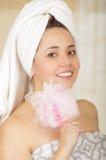 Beautiful fresh young girl wearing towel holding pink loofah body sponge. Close up shot of beautiful fresh young brunette girl wearing towel holding pink loofah Stock Photo