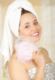 Beautiful fresh young girl wearing towel holding pink loofah body sponge. Close up shot of beautiful fresh young brunette girl wearing towel holding pink loofah Royalty Free Stock Photo
