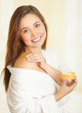 Beautiful fresh young girl wearing white bathrobe applying cream Royalty Free Stock Photography