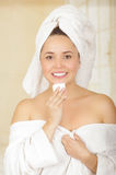 Beautiful fresh young girl wearing white bathrobe removing makeup Royalty Free Stock Photo