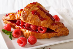 Beautiful freshly baked croissant stuffed with fresh raspberries. And jam close-up on the table. horizontal Royalty Free Stock Photo