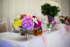 Beautiful freshly cut flowers in a glass vase on wedding recepti Royalty Free Stock Photography