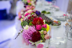 Beautiful freshly cut flowers in a glass vase on wedding recepti Stock Photo