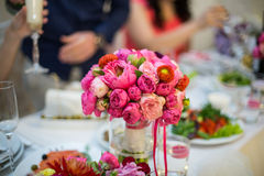 Beautiful freshly cut flowers in a glass vase on wedding recepti Stock Image