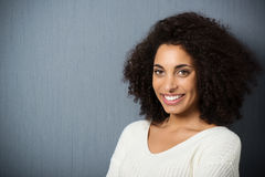 Beautiful friendly African American woman. Head and shoulders portrait of a beautiful friendly African American woman with a curly afro hairstyle looking at the Royalty Free Stock Photography
