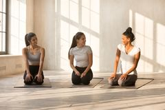 Pretty women talking sitting on yoga mat before starting trainin stock photography