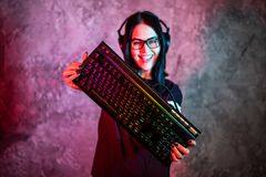 Beautiful Friendly Pro Gamer Streamer Girl Posing With a Keyboard in Her Hands, Wearing Glasses. Attractive Geek Girl. With Cool Neon Retro Colors in Background royalty free stock photo