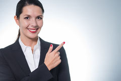 Beautiful friendly woman pointing to copy-space Stock Photo