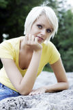 Beautiful friendly young blond woman. With a trendy short hairstyle reclining on a rock resting her chin on her hand smiling at the camera royalty free stock images