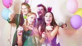 Beautiful friends having fun in party photo booth