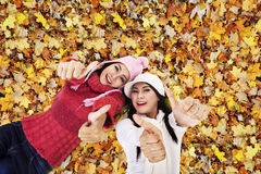 Beautiful friends laying on Autumn leaves Stock Photo
