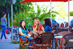Beautiful friends sitting on cafe terrace. Beautiful female friends sitting on cafe terrace stock images