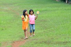 Beautiful friendship. Moments. Two girls walking on a green meadow. They are  best friends and sharing a story together Stock Photo