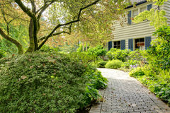 Beautiful front yard with walkway and grey brown large house. Royalty Free Stock Photography
