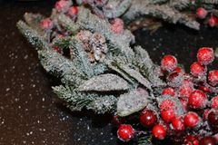 Frosty christmas wreath. A beautiful frosty Christmas wreath of spruce, red berries, green leaves and cones Royalty Free Stock Image