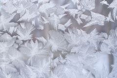 Beautiful frosty pattern in form of huge pointed snowflakes on window glass. Stock Photo