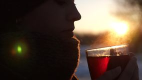 Beautiful frozen girl drinking tea from transparent glass outdoors in glare of setting sun. Woman froze in winter in cold and warms herself with cup of tea Royalty Free Stock Images