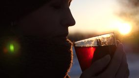 Beautiful frozen girl drinking tea from transparent glass outdoors in glare of setting sun. Woman froze in winter in cold and warms herself with cup of tea Royalty Free Stock Photos