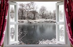 Beautiful frozen lake scene through an open window. View through open window onto a beautiful frozen lake winter snow in rural England. Red curtains hang in Stock Image