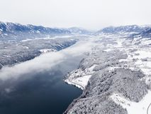 Snow covered winter landscape, cloud over a large lake. Royalty Free Stock Image