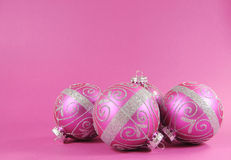Beautiful fuchsia pink festive bauble ornaments on a feminine pink background with copy space. For Merry Christmas or Happy Holidays seasons greetings Royalty Free Stock Photography
