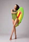 Beautiful full body brunette young woman walking with long hair. And surfboard over a gray background Stock Images