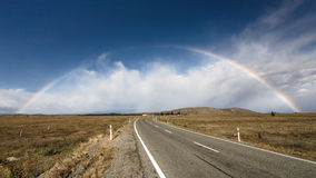 Beautiful full double rainbow over road. Beautiful full rainbow over road and mountain, New Zealand Stock Photo