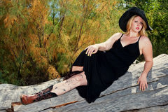 Beautiful full figured blonde woman outdoors. Beautiful full figured blonde woman wearing black dress resting on a log. She is wearing cowboy boots, and it is Royalty Free Stock Photography