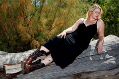 Beautiful full figured blonde woman outdoors. Beautiful full figured blonde woman wearing black dress resting on a log. She is wearing cowboy boots, and it is Royalty Free Stock Photo