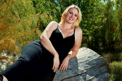 Beautiful full figured blonde woman outdoors. Beautiful full figured blonde woman wearing black dress resting on a log. She is wearing cowboy boots, and it is Stock Photos