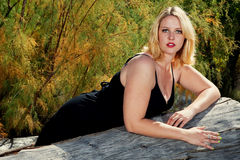Beautiful full figured blonde woman outdoors. Beautiful full figured blonde woman wearing black dress resting on a log. She is wearing cowboy boots, and it is Stock Images