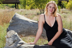 Beautiful full figured blonde woman outdoors. Beautiful full figured blonde woman wearing black dress resting on a log. She is wearing cowboy boots, and it is Royalty Free Stock Images