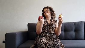 Beautiful full girl with apple and cake, choice slow-motion stock video footage