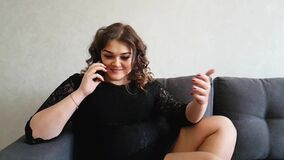 Beautiful full girl speaks on the phone on the couch. Dialogue stock video