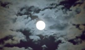 Beautiful full moon and white cloudy sky background in the midnight sky background, moonlight on Halloween night without stars. Full moon and white cloud sky in Stock Photo