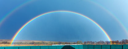 Beautiful Full Rainbow above Farm Field at Spring stock images