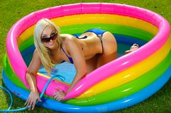 Beautiful fun bikini girl. Playing in kiddies pool Stock Photography