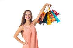 Beautiful fun girl raised high in a lot of different gift packages hand isolated on white background Stock Images