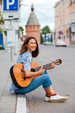 Fun smiling woman with a guitar sits on the curb Royalty Free Stock Photos