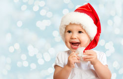 Beautiful funny baby in a Christmas hat  on blue Stock Photography