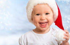 Beautiful funny baby in a Christmas hat  on blue Stock Images