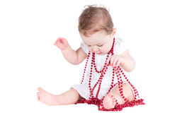 Beautiful funny baby girl playing with a red necklace Royalty Free Stock Images