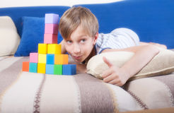 Beautiful funny blond boy lying on a cozy sofa. Showing colorful cubes and thumbs up Royalty Free Stock Photos