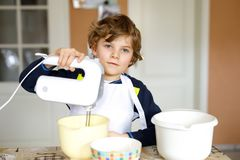 Beautiful funny blond little kid boy baking chocolate cake and tasting dough in domestic kitchen Stock Images