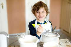Beautiful funny blond little kid boy baking chocolate cake and tasting dough in domestic kitchen Stock Image