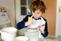 Beautiful funny blond little kid boy baking chocolate cake and tasting dough in domestic kitchen. Happy child having fun with working with mixer, flour, eggs Royalty Free Stock Image