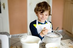Beautiful funny blond little kid boy baking chocolate cake and tasting dough in domestic kitchen. Happy child having fun with working with mixer, flour, eggs Stock Photos