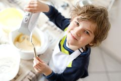 Beautiful funny blond little kid boy baking chocolate cake and tasting dough in domestic kitchen. Happy child having fun with working with mixer, flour, eggs Stock Photo