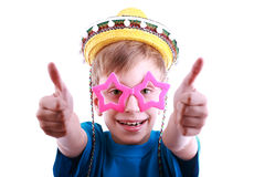 Beautiful funny boy in a blue t-shirt wearing colorful stylish star-shaped and glasses and yellow sombrero hat shows thumbs Royalty Free Stock Photo