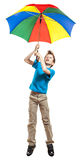 Beautiful funny boy in t-shirt flying with a multicolored umbrella Royalty Free Stock Images